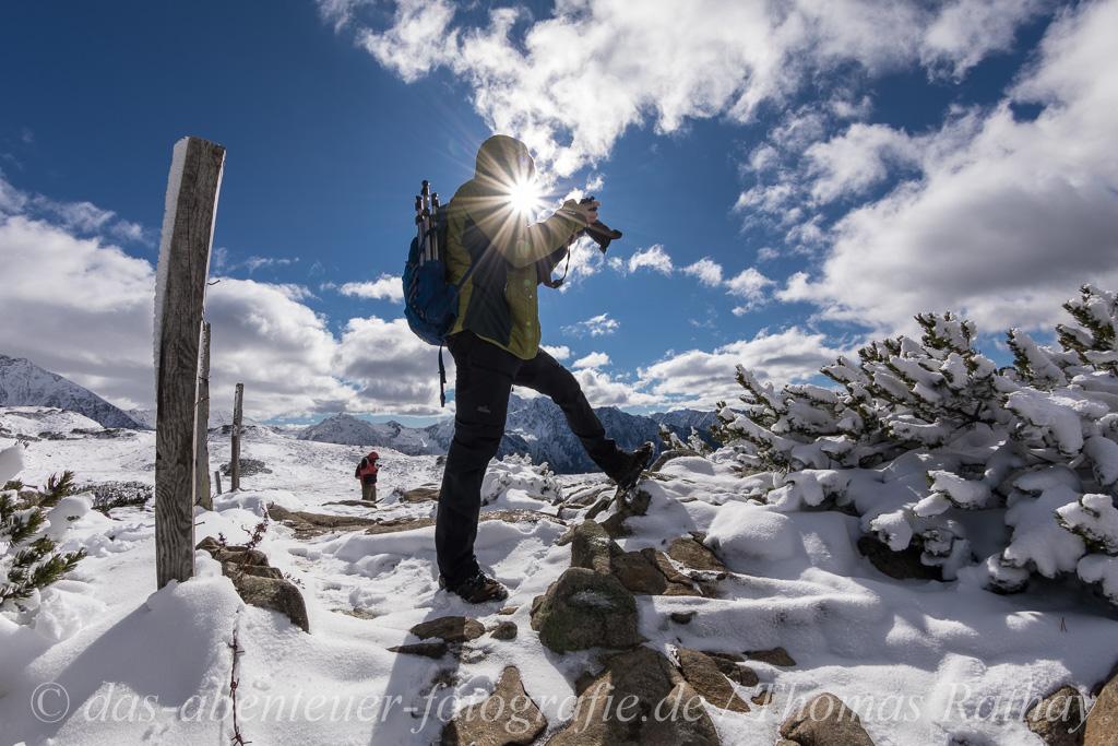 Mann steht im Sonnenlicht und fotografiert